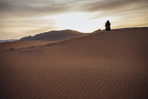 Rear view of woman photographing through mobile phone at desert during sunset - CAVF30720