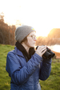 Woman holding binoculars looking away while standing on grassy field - CAVF30759