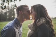 Couple kissing while standing on grassy field against sky - CAVF30813