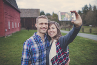 Happy couple taking selfie while standing on grassy field - CAVF30819