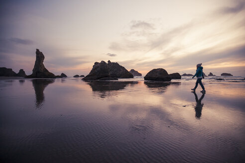 Full length of woman walking at Bandon beach against sky during sunset - CAVF30822
