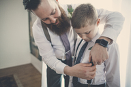 Bridegroom assisting pageboy in getting dressed at home - CAVF30837