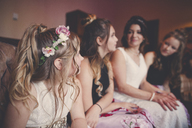 Bride with bridesmaids and flower girl sitting at home - CAVF30840