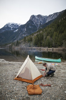 High angle view of man making tent at lakeshore against mountains - CAVF30870