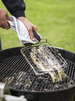 Man preparing grilled fish for midsummer celebrations - FOLF02797