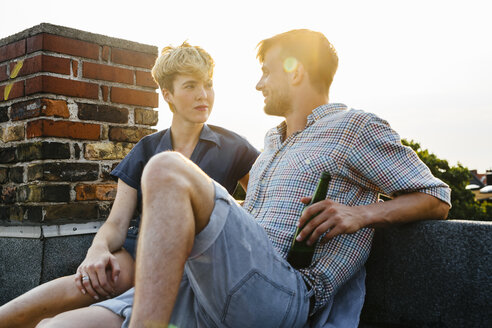 Young couple sitting on rooftop holding beer - FOLF02908