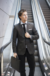 Businessman standing by escalator - FOLF02998