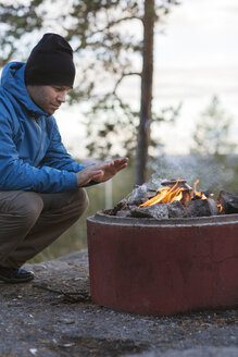 Mid adult man crouching by campfire - FOLF03193