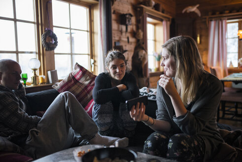 Young woman showing smart phone to friends in log cabin - FOLF03331
