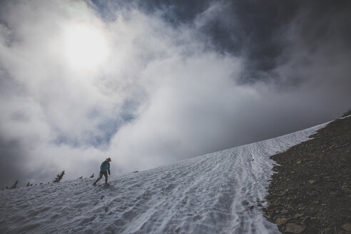 Low angle view of female hiker hiking on snow against cloudy sky - CAVF30920