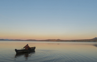 High angle view of man in boat on lake against clear sky during sunset - CAVF31151