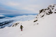 Hiker on snow covered mountain against cloudy sky - CAVF31157