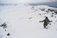 Rear view of hiker running down on snow covered mountain against sky - CAVF31160