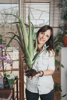Portrait of smiling woman holding an aloe vera - SKCF00358