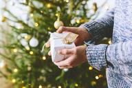 Man holding christmas gift against christmas tree - FOLF03644