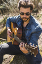 Young man playing guitar outdoors - AFVF00379