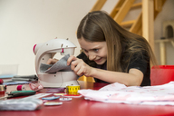 Smiling girl using sewing machine - SARF03628
