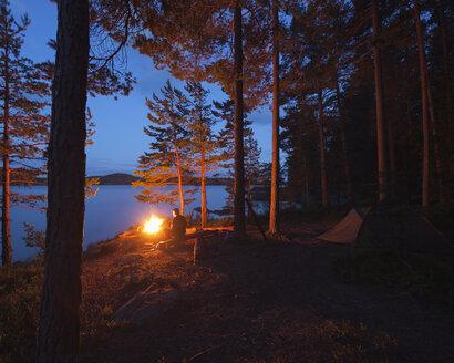 Man by bonfire on riverbank - FOLF03878