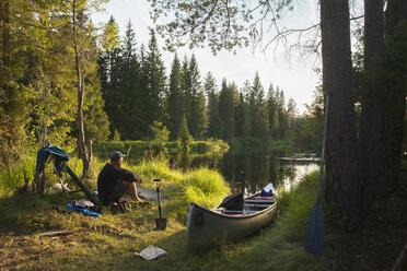 Man sitting by canoe on riverbank - FOLF03881