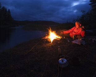 Man by bonfire on riverbank - FOLF03887