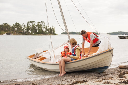 Family with child wearing life jackets on sailboat - FOLF03896