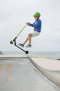 Young boy jumping on ramp on push scooter - FOLF03959