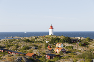 Lighthouse on rocks on Baltic sea with red cottages on foreground - FOLF04202