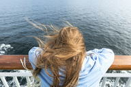 Rear view of blonde girl leaning on railing on cruise ship - FOLF04274