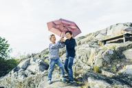 Laughing boys with umbrella on rocky hill - FOLF04286