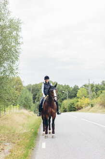 Mid adult woman riding horse on road through forest - FOLF04313
