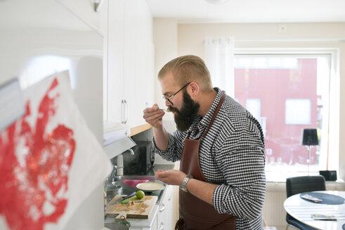 Man tasting food in domestic kitchen - FOLF04439