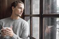 Man holding mug and looking through window - FOLF04481