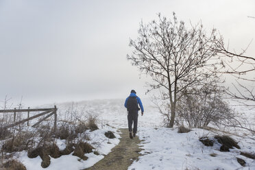Man walking on a snowy trail - FOLF04790
