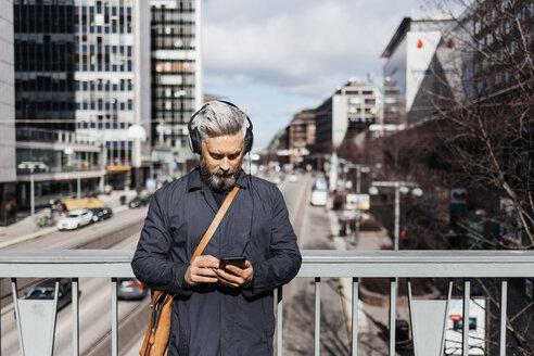 Man on smart phone on street in Stockholm, Sweden - FOLF04853