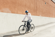 Man on smart phone while bicycling - FOLF04919