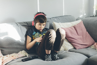 Boy with headphones sitting on sofa - FOLF05114