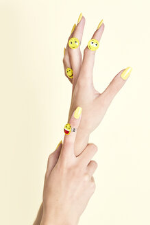 Close-up of woman's hands with emojis on rings - SRYF00783