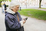 Senior woman standing and using smartphone - FOLF05360