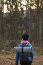 Rear view of woman hiking through forest in Lerum, Sweden - FOLF05465