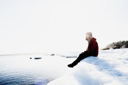Man sitting on ice by sea - FOLF05483