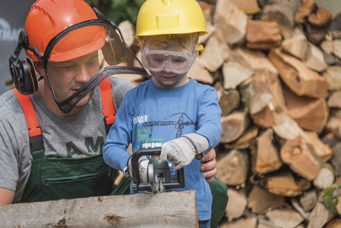 Father and son sawing wood together - PAF01789