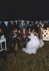 Happy wedding couple having fun sitting on sofa with their friends on a night field party - DAPF00933