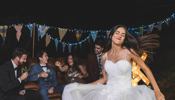 Happy bride dancing on a night field party with groom and friends in the background - DAPF00936