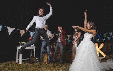 Surprised bride looking at man jumping on a night field party with friends - DAPF00942