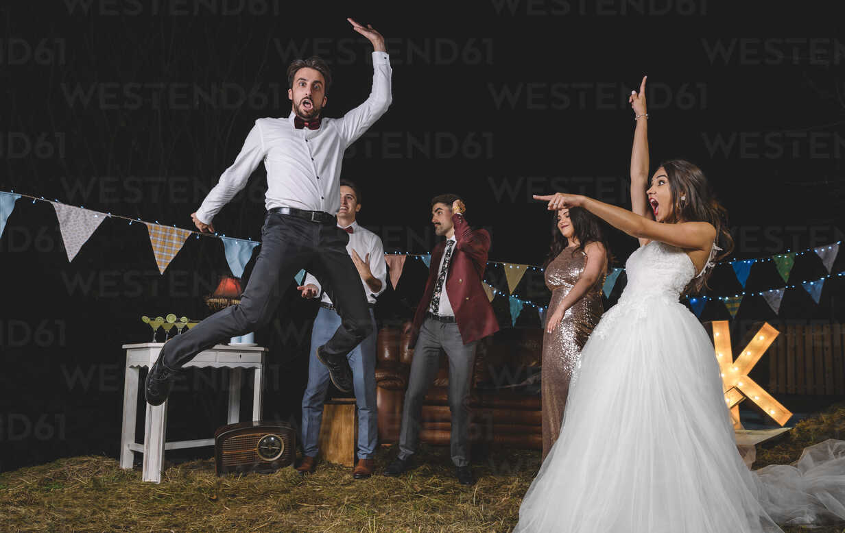Surprised bride looking at man jumping on a night field party with friends - DAPF00942 - David Pereiras/Westend61