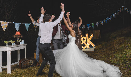 Happy bride and friends with arms raised dancing and having fun on a night field party - DAPF00945