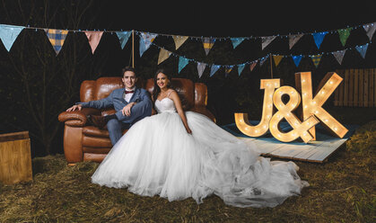 Portrait of happy wedding couple sitting on sofa on a night field party - DAPF00948