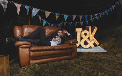 Portrait of man in suit posing on sofa on a night field party - DAPF00951