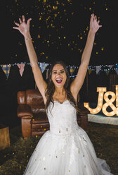 Cheerful bride raising her arms while confetti falling over her on a night party outdoors - DAPF00954