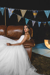 Serious bride lying on sofa on a night field party - DAPF00957